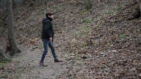 Giovane turbato che cammina nella foresta, pietra di lancio con il disturbo, rabbia impotente video d archivio