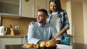 Giovane turbato che legge le fatture non pagate ed abbracciato dalla sua moglie che lo sostiene nella cucina a casa immagine stock