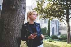 Giovane turista affascinante della donna con il telefono delle cellule in mani che riposano dopo il giro Immagini Stock