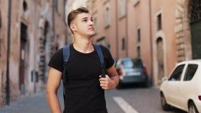 Giovane turista attraente con uno zaino che cammina sulla via della città piacevole e che guarda intorno esterno video d archivio