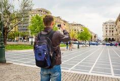 Giovane turista con lo zaino che prende le immagini degli agora quadrati di un Archeas e di una via pedonale su uno smartphone a  immagine stock libera da diritti