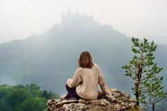 Giovane turista femminile che considera il castello famoso di Hohenzollern in nebbia spessa, Germania fotografia stock libera da diritti