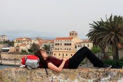 Giovane turista femminile che si rilassa sul suo zaino, Alghero, Sardegna, Italia Immagini Stock Libere da Diritti