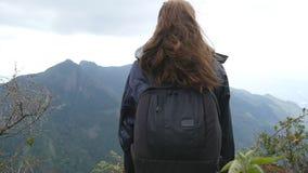 Giovane turista femminile con lo zaino che gode di bella vista nelle montagne Viaggiatore della donna in impermeabile che sta sul stock footage