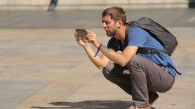 Giovane turista maschio curioso che prende le immagini sul quadrato di città con il telefono cellulare video d archivio