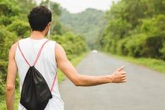Giovane turista sui voti hitckhiking della donna della strada sulla strada Bella ragazza sulla strada Un uomo va sulla vacanza, f fotografia stock libera da diritti