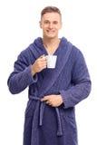 Giovane in un accappatoio blu che tiene una tazza da caffè Fotografia Stock