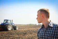 Giovane in un campo e un trattore su un fondo Fotografie Stock Libere da Diritti