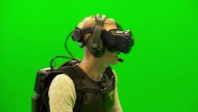 Giovane in un casco di VR negli obiettivi del cammuffamento da una pistola archivi video