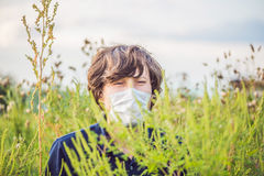 Giovane in una maschera medica a causa di un'allergia all'ambrosia Fotografie Stock Libere da Diritti