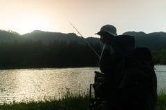 Giovane in una sedia a rotelle che pesca nel bello lago nel tramonto, alba immagine stock