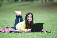 Giovane università o studente di college femminile asiatica che si trova sullo stomaco in parco Fotografia Stock
