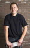Giovane uomo adulto casuale che si leva in piedi vicino al muro di mattoni Immagine Stock Libera da Diritti