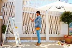 Giovane uomo adulto che costruisce la parete di legno della pergola sulla zona del patio del tetto Fotografia Stock Libera da Diritti