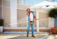Giovane uomo adulto che costruisce la parete di legno della pergola sulla zona del patio del tetto Immagini Stock
