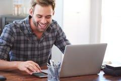 Giovane uomo adulto felice che sorride mentre esaminando il suo telefono Fotografie Stock Libere da Diritti