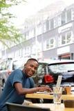 Giovane uomo africano al caffè con il computer portatile Fotografia Stock Libera da Diritti