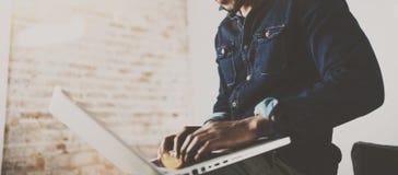 Giovane uomo africano barbuto che per mezzo del computer portatile mentre sedendosi al suo posto coworking moderno Concetto della Immagini Stock
