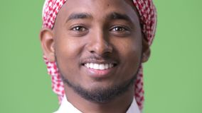 Giovane uomo africano bello che indossa i vestiti musulmani tradizionali contro il fondo verde stock footage