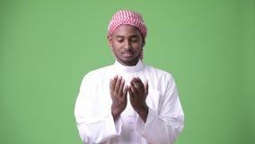 Giovane uomo africano bello che indossa i vestiti musulmani tradizionali contro il fondo verde video d archivio