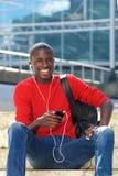 Giovane uomo africano bello con il telefono cellulare Fotografia Stock