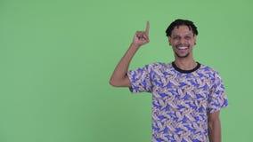 Giovane uomo africano bello felice che indica su e che sembra emozionante stock footage