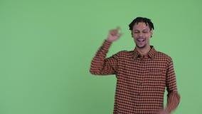 Giovane uomo africano bello felice che indica su e che sembra emozionante archivi video