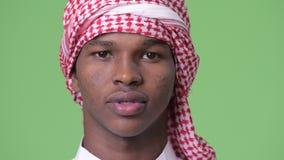 Giovane uomo africano che indossa i vestiti musulmani tradizionali contro il fondo verde archivi video