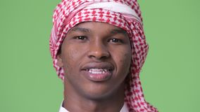 Giovane uomo africano che indossa i vestiti musulmani tradizionali contro il fondo verde stock footage