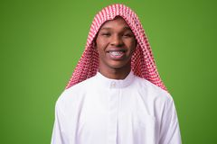 Giovane uomo africano che indossa i vestiti musulmani tradizionali contro il gre fotografie stock libere da diritti