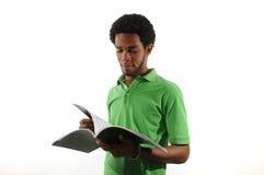 Giovane uomo africano che legge uno scomparto fotografia stock