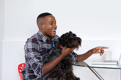 Giovane uomo africano che mostra qualcosa sul computer portatile al suo cane di animale domestico Fotografie Stock Libere da Diritti