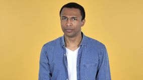 Giovane uomo africano che scuote testa per rifiutare, fondo giallo video d archivio