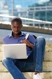 Giovane uomo africano che si siede all'aperto e che per mezzo del computer portatile Immagine Stock