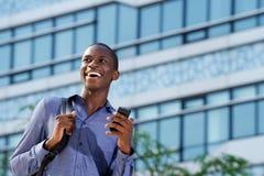 Giovane uomo africano che sorride all'aperto con il telefono cellulare Immagini Stock