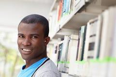 Giovane uomo africano che sorride nella libreria Fotografie Stock Libere da Diritti
