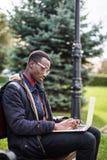 Giovane uomo africano con il computer portatile che si siede su un banco di legno e su una battitura a macchina Fotografie Stock