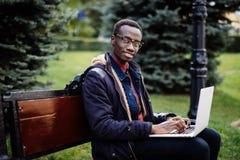 Giovane uomo africano con il computer portatile che si siede su un banco di legno e su una battitura a macchina Immagini Stock Libere da Diritti