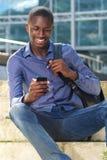 Giovane uomo africano con il telefono cellulare Fotografia Stock