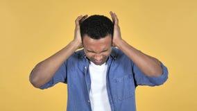 Giovane uomo africano con l'emicrania, fondo giallo stock footage