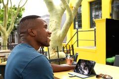 Giovane uomo africano felice ad un caffè con la linguetta digitale Fotografia Stock Libera da Diritti