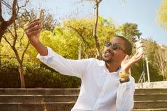 Giovane uomo africano felice in camicia bianca e parlare sul telefono cellulare e gesturing mentre sedendosi all'aperto Fotografie Stock Libere da Diritti