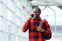 Giovane uomo africano felice che parla sul telefono all'aperto Fotografia Stock Libera da Diritti