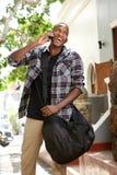 Giovane uomo africano felice che parla sul telefono cellulare Fotografia Stock Libera da Diritti