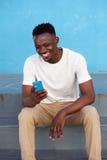 Giovane uomo africano felice che si siede sui punti e che per mezzo del telefono Fotografia Stock Libera da Diritti