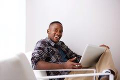 Giovane uomo africano felice sulla sedia del bracciolo con un computer portatile Fotografia Stock