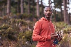 Giovane uomo africano messo a fuoco che ascolta la musica prima di un funzionamento Fotografia Stock Libera da Diritti