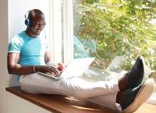 Giovane uomo africano rilassato sorridente che per mezzo del computer portatile con le cuffie che si siedono sul davanzale della  Fotografia Stock