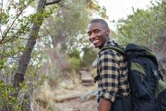 Giovane uomo africano sorridente che fa un'escursione nelle colline Fotografia Stock Libera da Diritti