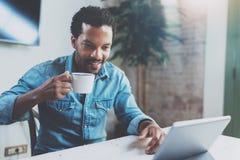 Giovane uomo africano sorridente che fa video conversazione tramite compressa digitale con gli amici mentre bevendo caffè nero in Fotografia Stock
